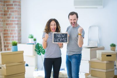 couple holding blackboard moving to a new home screaming proud and celebrating victory and success very excited, cheering emotion